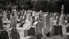 Het zwart-wit kerkhof met het oude grafstenen angstaanjagend geven voelt Stock Foto's