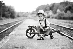 Het zwart-wit portret van het leuke jongen dragen in retro stijlzitting op station en wacht op iets stock foto