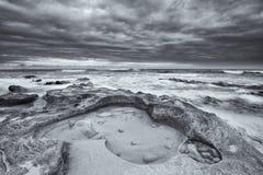 Het zwart-witte landschap van oceaanrotsen en artistieke de wolken bedriegen Royalty-vrije Stock Afbeelding