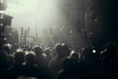 Het zwart-witte silhouet van mensen overbevolkt het lopen onderaan de voetstraat onder de zonneschijn stock afbeelding