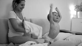 Het zwart-witte vrolijke peuterjongen spelen in bed met jonge glimlachende moeder bij nacht stock foto