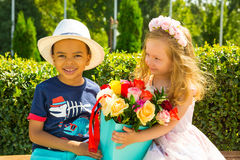 Het zwarte Afrikaanse Amerikaanse jongensjonge geitje geeft bloemen aan meisjeskind op verjaardag Kleine aanbiddelijke kinderen i Royalty-vrije Stock Foto