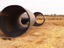 Het zwarte door buizen leiden bij bouwwerf Royalty-vrije Stock Foto