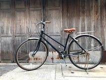 Het zwarte fiets bruine kussen de voordeur van het huis en de oude houten muur is niet geschilderd met een eenvoudig het levensco Stock Foto