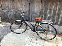 Het zwarte fiets bruine kussen de voordeur van het huis en de oude houten muur is niet geschilderd met een eenvoudig het levensco Royalty-vrije Stock Foto's
