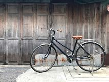 Het zwarte fiets bruine kussen de voordeur van het huis en de oude houten muur is niet geschilderd met een eenvoudig het levensco Stock Fotografie
