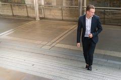 Het zwarte kostuum die van de zakenmanslijtage opvoerend trede in modern lopen royalty-vrije stock fotografie