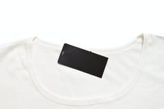 Het zwarte lege prijskaartje hing over witte t-shirt. Stock Foto