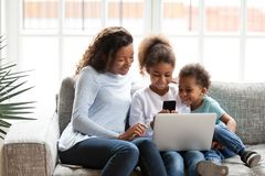 Het zwarte mamma heeft pret die met jonge geitjes gadgets thuis gebruiken stock foto