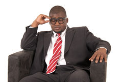 Het zwarte mannelijke model nadenken terwijl de zitting stoel die een kostuum dragen is Stock Fotografie