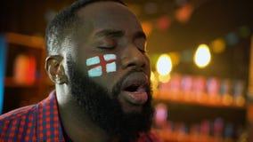Het zwarte mannetje met Engelse vlag schilderde op de wang teleurgestelde mislukking van het voetbalteam stock video