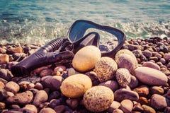 Het zwarte masker voor het duiken en een buis voor ademhaling onder het water liggen op de kust tegen de achtergrond van overzees stock fotografie
