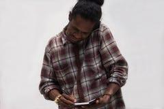 Het zwarte mens nemen neemt van terwijl het spreken op telefoons, jonge de mensenbespreking van Papoea met smartphone nota terwij royalty-vrije stock afbeelding