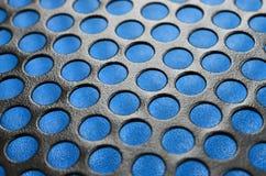 Het zwarte netwerk van het het gevalpaneel van de metaalcomputer met gaten op blauwe backgrou Stock Afbeeldingen