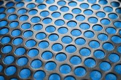 Het zwarte netwerk van het het gevalpaneel van de metaalcomputer met gaten op blauwe backgrou Royalty-vrije Stock Afbeeldingen