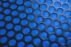 Het zwarte netwerk van het het gevalpaneel van de metaalcomputer met gaten op blauwe backgrou Stock Foto
