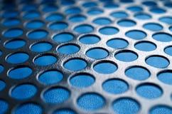 Het zwarte netwerk van het het gevalpaneel van de metaalcomputer met gaten op blauwe backgrou Stock Foto's
