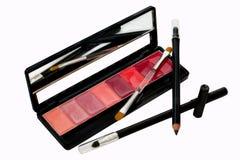Het zwarte potlood van de oogvoering met lippenstift en borstel stock afbeeldingen