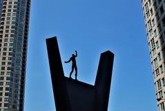 Het zwarte silhouet van een acrobaat die op een voetstuk in evenwicht brengen Royalty-vrije Stock Foto