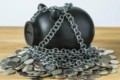 Het zwarte spaarvarken met kettingen bovenop muntstukken als veiligheid beschermt Royalty-vrije Stock Afbeelding