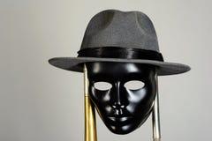 Het zwarte theatermasker en hoed hangen op een messingspijp Stock Fotografie