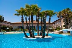 Het zwembad van het hotel met het palmeiland Stock Afbeeldingen