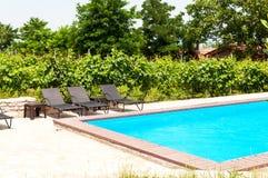 Het zwembad van ligstoelen dichtbij Stock Foto