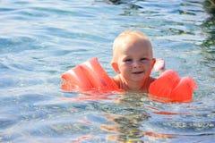 Het zwemmen van de baby in het overzees Stock Foto's