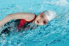 Het zwemmen van het meisje de slag of kruipt in pool Stock Afbeelding