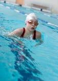 Het zwemmen van het meisje schoolslag in pool Royalty-vrije Stock Afbeelding