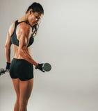 Het zweten vrouwelijke atleten opheffende domoor Stock Afbeeldingen