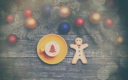 Hete cappuccino met de vorm van de Kerstmisboom op een houten lijst dichtbij Royalty-vrije Stock Foto's