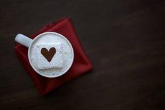 Hete Chocolade met Cacao Bestrooide Hartheemst op Rood Servet Stock Afbeelding