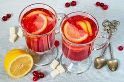 Hete de winter gezonde drank - Amerikaanse veenbesthee of sangria met verse citroenplakken in glazen op de grijze concrete keuken stock afbeelding