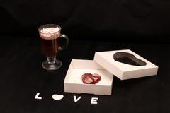 hete drank in een glaskop met roze heemst en witte doos met een transparante dekking in de vorm van hart met koekjes stock foto's