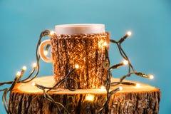 Hete drank in kop met wollen sweater en Kerstmislichten op houten logboek stock foto