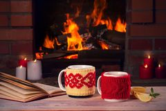Hete dranken in mokken, boek en kaarsen op houten lijst naast comfortabele open brandplaats De herfst of de wintervakantieconcept royalty-vrije stock foto's