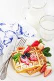 Hete eigengemaakte Belgische wafels met bessen en melk op lichte rug Royalty-vrije Stock Afbeeldingen