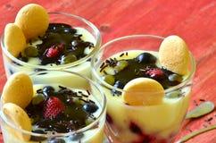 Hete eigengemaakte vanillepudding met aardbeien en wijnstokbessen Stock Afbeelding