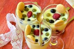 Hete eigengemaakte vanillepudding met aardbeien en wijnstokbessen Stock Foto's