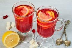 Hete gezonde Amerikaanse veenbesthee of detox de winterdrank - sangria met verse citroenen in glazen op de grijze concrete achter stock fotografie