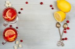 Hete gezonde de winterdrank - detox Amerikaanse veenbesthee of sangria met verse citroenplakken in glazen op de grijze concrete a stock foto's