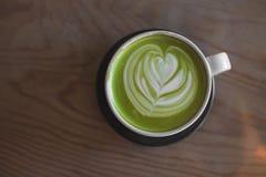 Hete groene thee latte kunst op de winkel van de lijstkoffie stock fotografie