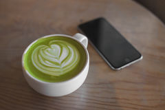 Hete groene thee latte kunst op hand op de winkel van de lijstkoffie stock fotografie