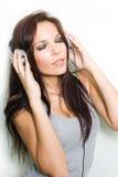 Hete jonge brunette die van muziek geniet. Stock Afbeeldingen