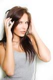 Hete jonge brunette die zilveren headhones draagt. Stock Afbeelding