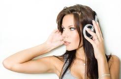 Hete jonge brunette die zilveren headhones draagt. Stock Fotografie