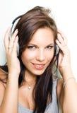 Hete jonge brunette die zilveren headhones draagt. Royalty-vrije Stock Foto's