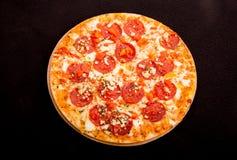 Hete Kaasachtige Pepperonispizza op Zwarte Achtergrond Royalty-vrije Stock Afbeeldingen