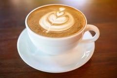 Hete koffie latte kop op houten lijstachtergrond met warme ochtend Stock Foto